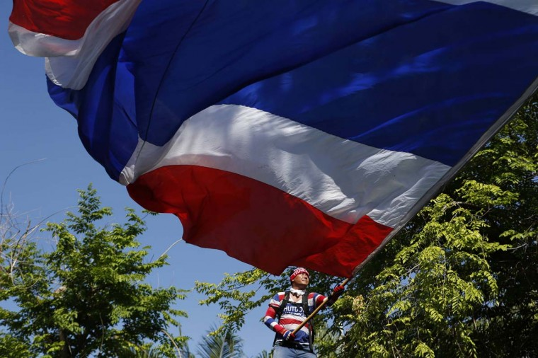 An anti-government protester waves a Thai flag as he gathers with others outside the Parliament House in Bangkok on May 9. Ousted Prime Minister Yingluck Shinawatra's Puea Thai Party still runs the interim government and is hoping to organise a July 20 election that it would probably win, but the protesters want the government out, the election postponed and reforms to end the influence of Yingluck's brother, former premier Thaksin Shinawatra. Protest leader Suthep Thaugsuban, speaking to supporters in a city park, urged them to rally outside parliament, the prime minister's offices and five television stations to prevent them being used by the government.   || PHOTO CREDIT: ATHIT PERAWONGMETHA  - REUTERS