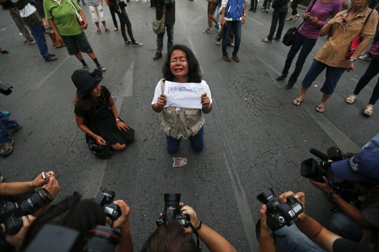 Reporters take pictures of a protester against military rule holding a sign at the Victory Monument in Bangkok May 26, 2014. Thai coup leader General Prayuth Chan-ocha said on Monday he had been formally endorsed by the king as head of a military council that will run the country, and warned he would use force if political protests flared up again. (REUTERS/Damir Sagolj)