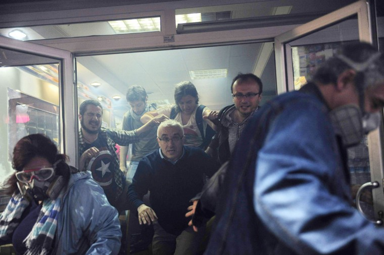 People try to escape from a cafe, after tear gas fired by riot police outside to disperse protesters seeped in, at central Istanbul. Turkish police fired teargas and water cannon on Saturday to disperse protesters in central Istanbul who sought to mark the one-year anniversary of the country's biggest anti-government demonstrations in decades. (Yagiz Karahan/Reuters)