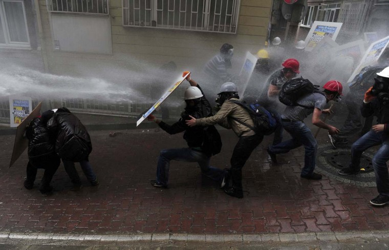 Protesters shield themselves as riot police use water cannon to disperse them during a May Day demonstration in Istanbul. Turkish police fired water cannon and tear gas on Thursday to prevent hundreds of protesters from defying a ban on May Day rallies and reaching Istanbul's central Taksim Square, the focal point of weeks of protests last summer.    || PHOTO CREDIT: YAGIZ KARAHAN  - REUTERS