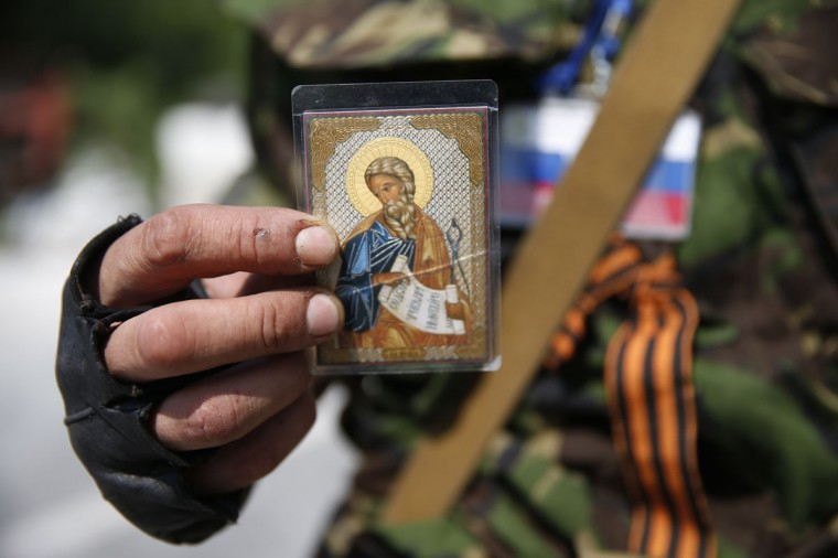 A member of a newly-formed pro-Russian armed group called the Russian Orthodox Army shows an Orthodox icon as he mans a barricade near Donetsk airport May 29, 2014. Pro-Russian separatists shot down a Ukrainian army helicopter on Thursday, killing 14 soldiers including a general, as government forces pressed ahead with an offensive to crush rebellions in the east swiftly following the election of a new president. REUTERS/Maxim Zmeyev