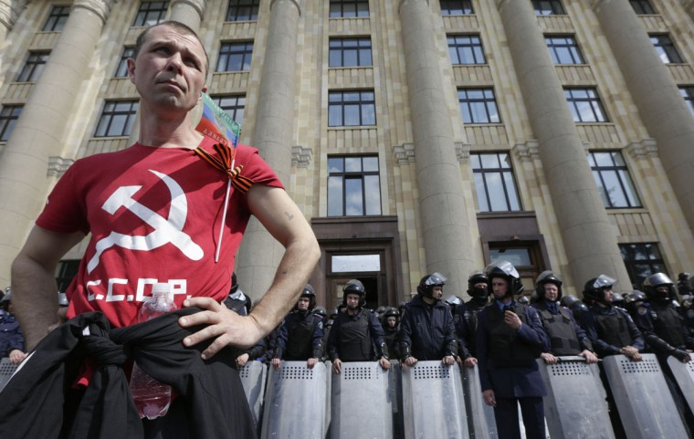 A Communist supporter stands near a police line guarding the regional administration building during a May Day rally in the eastern Ukrainian city of Kharkiv, May 1, 2014. (REUTERS/Konstantin Chernichkin)