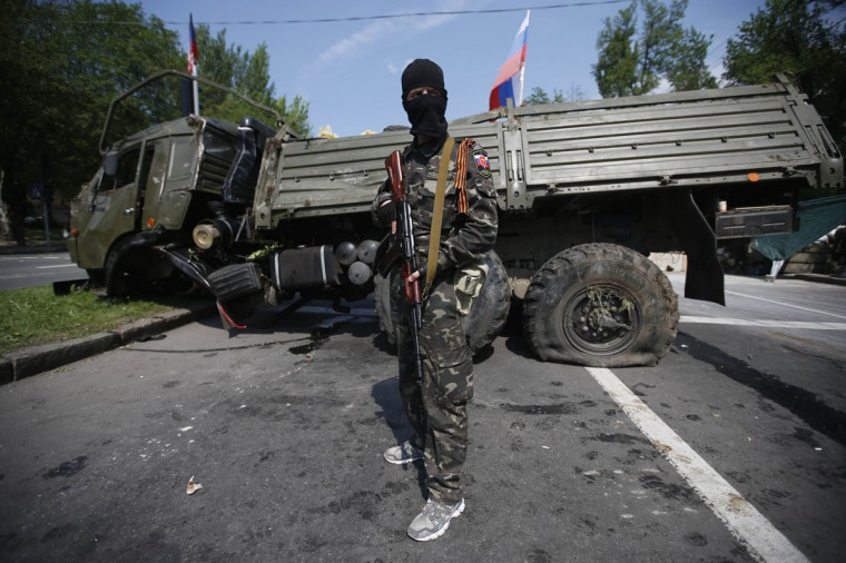 A member of a newly-formed pro-Russian armed group called the Russian Orthodox Army stands guard at a barricade near a destroyed transport vehicle near Donetsk airport May 29, 2014. Pro-Russian separatists shot down a Ukrainian army helicopter on Thursday, killing 14 soldiers including a general, as government forces pressed ahead with an offensive to crush rebellions in the east swiftly following the election of a new president. . Pro-Russian separatists shot down a Ukrainian army helicopter on Thursday, killing 14 soldiers including a general, as government forces pressed ahead with an offensive to crush rebellions in the east swiftly following the election of a new president. REUTERS/Maxim Zmeyev