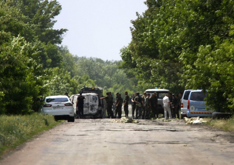 Ukrainian soldiers survey an area where pro-Russian rebels killed thirteen Ukrainian servicemen on the outskirts of the eastern Ukrainian town of Volnovakha, south of Donetsk May 22, 2014. The clash, one of several overnight in the region, came three days before Ukrainians vote in a presidential election billed as the most crucial since the country gained independence from Moscow in 1991. REUTERS/Yannis Behrakis