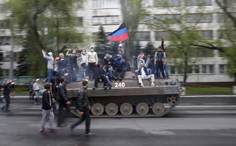 People ride on a towed broken armoured vehicle left behind after Ukrainian forces attacked police headquarters in an attempt to drive out pro-Russian militants in Mariupol on May 9. Ukrainian security forces killed about 20 pro-Russian rebels who tried to seize control of police headquarters in the eastern port city of Mariupol on Friday, the Interior Minister said.     || PHOTO CREDIT: MARKO DJURICA  - REUTERS