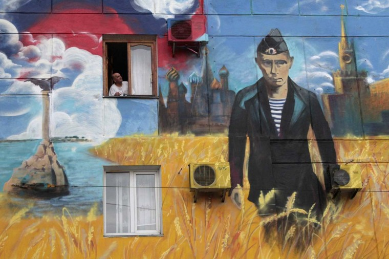 A man looks out of his window surrounded by a recently created graffiti depicting the Kremlin, Russia's President Vladimir Putin and the Russian flag, on the wall of a residential building in the Crimean port of Sevastopol May 13, 2014. (Stringer/Reuters)