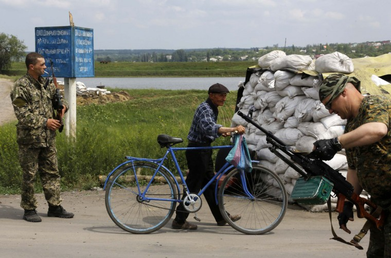 A local man pushes his bicycle as pro-Russian rebels provide security at a check point in the outskirts of the eastern Ukrainian town of Slaviansk May 15, 2014. (REUTERS/Yannis Behrakis)