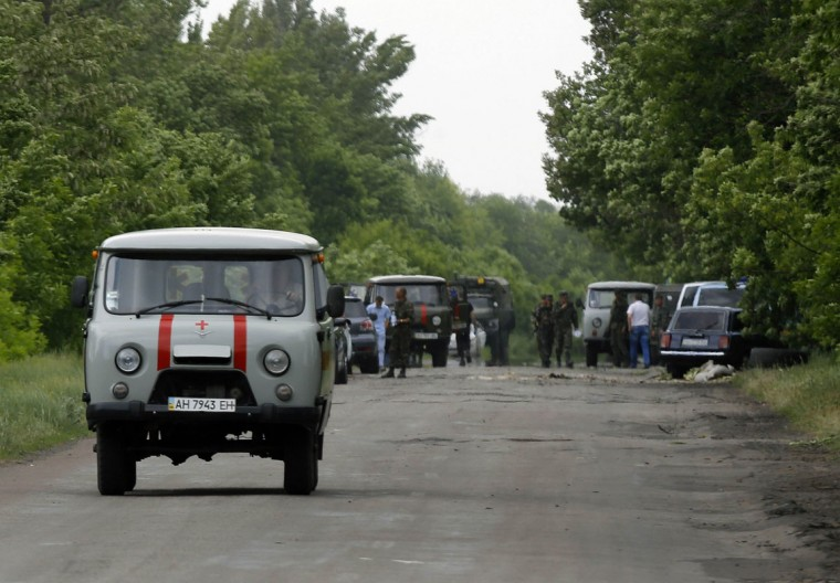 An ambulance carrying dead Ukrainian soldiers travels off the site (seen in background) where pro-Russian rebels killed thirteen Ukrainian servicemen on the outskirts of the eastern Ukrainian town of Volnovakha, south of Donetsk, May 22, 2014. The clash, one of several overnight in the region, came three days before Ukrainians vote in a presidential election billed as the most crucial since the country gained independence from Moscow in 1991. REUTERS/Yannis Behrakis