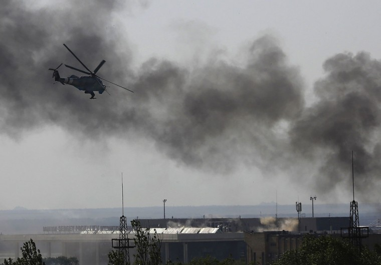 A Ukrainian helicopter Mi-24 gunship fires its cannons against rebels at the main terminal building of Donetsk international airport May 26, 2014. Three Ukrainian helicopter gunships mounted a heavy attack on the rebel-held international airport terminal at Donetsk on Monday, firing rockets and cannon and throwing out decoy flares as militants shot at them from the ground. (REUTERS/Yannis Behrakis)