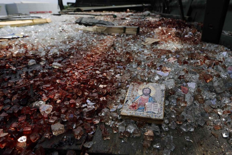 A bloodstained icon of Jesus is seen among blood soaked shattered glass atop a wrecked truck near the Donetsk airport May 27, 2014. The truck used to ferry their fighters was wrecked on the airport road, covered in blood and completely riddled with bullets. More than 50 pro-Russian rebels were killed in an unprecedented assault by Ukrainian government forces, which raged into a second day on Tuesday after a newly-elected president vowed to crush the revolt in the east once and for all. (Yannis Behrakis/Reuters)
