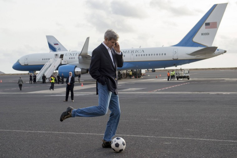 U.S. Secretary of State John Kerry kicks a soccer ball while talking on his cellphone during an airplane refuelling stop, while enroute to Washington, at Sal Island, Cape Verde. (Saul Loeb/Reuters)
