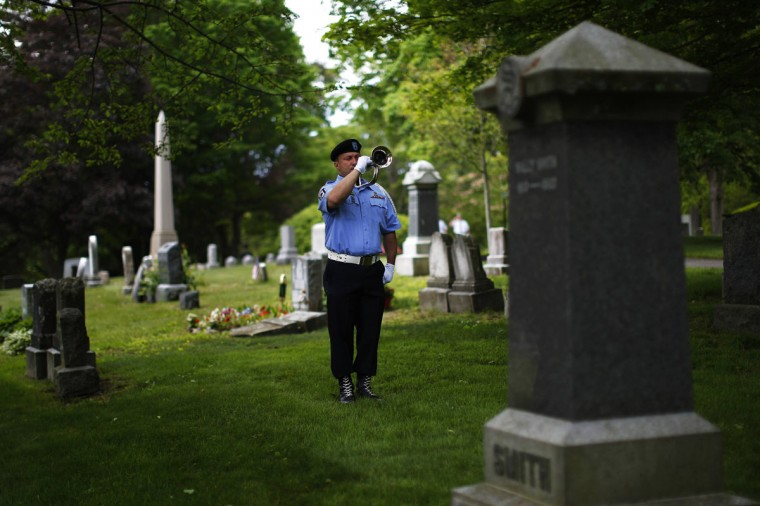 United States Army Desert Storm veteran Frank D'Amato plays taps during Memorial Day ceremonies at Cedar Grove Cemetery in Boston, Massachusetts May 26, 2014. (REUTERS/Brian Snyder)