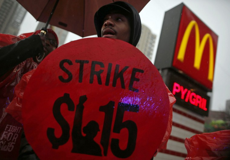 Demonstrators protest in front of a McDonald's restaurant in Chicago, Illinois, May 15, 2014. U.S. fast food workers seeking higher wages plan strikes and demonstrations on Thursday that could affect thousands of restaurants across the country the workers say make huge profits from paying them workers a pittance. (REUTERS/Jim Young)