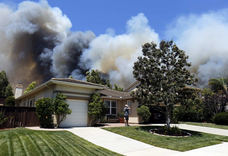 A man talks on a phone as a wildfire is seen approaching the neighborhood in Carlsbad, California. (Mike Blake/Reuters)