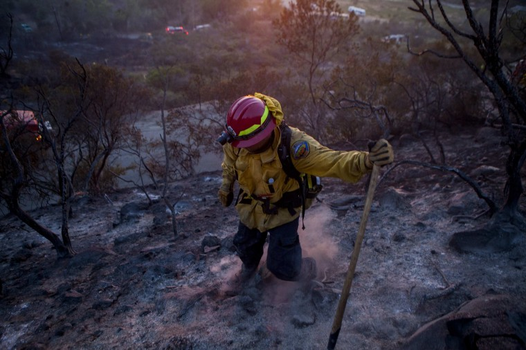 Fire crew put out smouldering embers from the Cocos Fire in San Marcos, California May 15, 2014. A towering wall of flames charged a hillside California community on Thursday as firefighters battled fierce wildfires that have forced 125,000 people to flee homes in the San Diego area and may have killed at least one person. (REUTERS/Sam Hodgson)