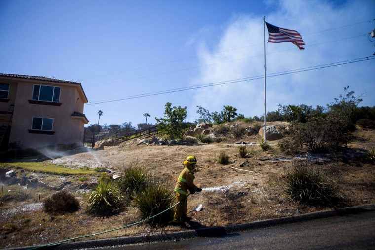 A firefighter sprays down a front lawn in the Cocos Fire in San Marcos, California, May 15, 2014. Wildfires were raging in southern California on Thursday, keeping thousands of residents and students away from their homes after San Diego county officials maintained evacuation advisories. (REUTERS/Sam Hodgson)