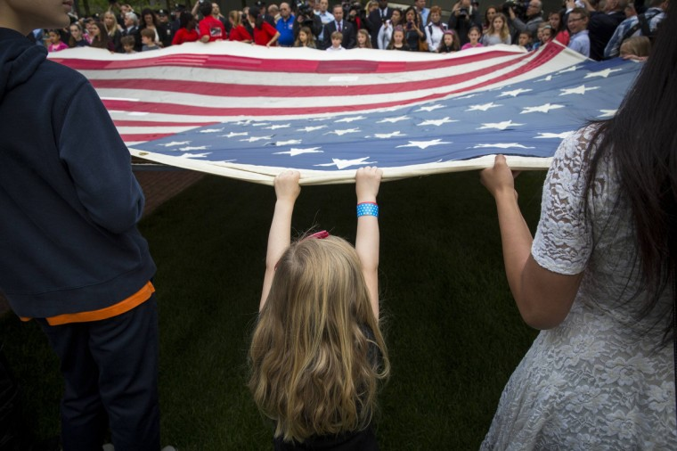 A girl designated to assist with transferring the National 9/11 Flag, donated by New York Says Thank You Foundation, holds it aloft on the grounds of the 9/11 Memorial Plaza before donating it to the National September 11 Memorial Museum in New York. Destroyed in the aftermath of the World Trade Center attacks on September 11 the flag has been stitched back together and has visited all 50 states. (Lucas Jackson/Reuters