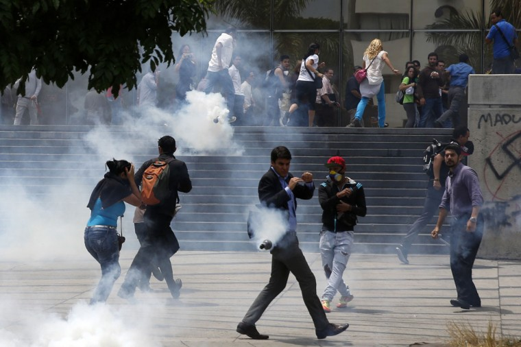 People run away from tear gas during a protest against President Nicolas Maduro's government in Caracas May 8, 2014. Venezuelan authorities on Thursday arrested hundreds of youth activists who had spent weeks in camps set up in public spaces as part of protests against President Nicolas Maduro, an effort to snuff out a waning three-month demonstration movement. (REUTERS/Carlos Garcia Rawlins)