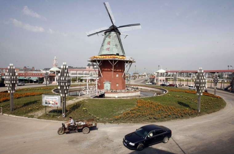 """A car drives on a roundabout with a windmill in the middle in """"Holland Village"""" in Shenyang, northeast China's Liaoning province September 8, 2007. """"Holland Village"""" is a place imitating Holland's architectural style, it occupies 2.2 square km and cost 7 billion yuan $929 million to build. The village consists of residential housing, gardens and tourist attractions, local media reported. (REUTERS/Stringer)"""