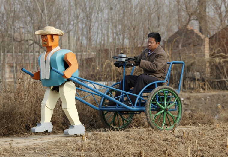 Farmer Wu Yulu drives his rickshaw pulled by a his home-made walking robot near his home in a village at the outskirts of Beijing on Jan. 8, 2009. This robot is the latest and largest development of hobby inventor Wu, who started to build robots in 1986, made of wire, metal, screws and nails found in rubbish sites. (REUTERS/Reinhard Krause)