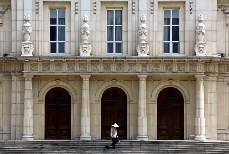 A cleaner works in front of a building that makes up the luxurious Chateau Laffitte Hotel, an imitation of the 1650 Château Maisons-Laffitte by the French architect François Mansart, located on the outskirts of Beijing August 20, 2010. (REUTERS/David Gray)