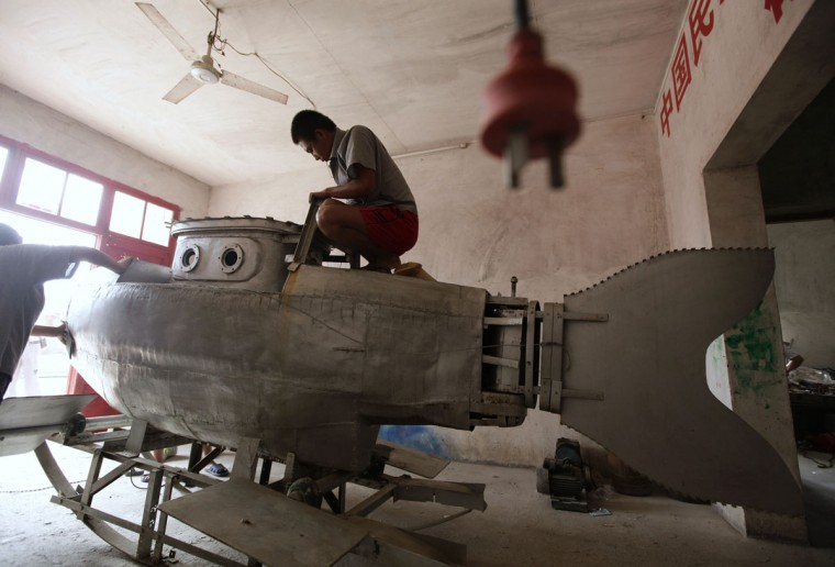 """A worker polishes the surface of an unfinished miniature submarine at a workshop of Zhang Wuyi, a local farmer who is interested in scientific inventions, in Qingling village, on the outskirts of Wuhan, capital of central China's Hubei province on Aug. 29, 2011. Zhang has successfully tested his home-made miniature submarine """"Shuguang Hao"""", which is 3.6 m (12 feet) long, 1.8 m (6 feet) high, has a maximum diving depth of 20 m (65 feet), can travel at a speed of 20 km per hour for 10 hours underwater and is shaped as a dolphin. """"I hope to sell my submarine as a civil product with the price of about 100,000 yuan ($15,670) after safety tests, and a merchant has decided to order one in this month"""", Zhang said. (REUTERS/Jason Lee)"""