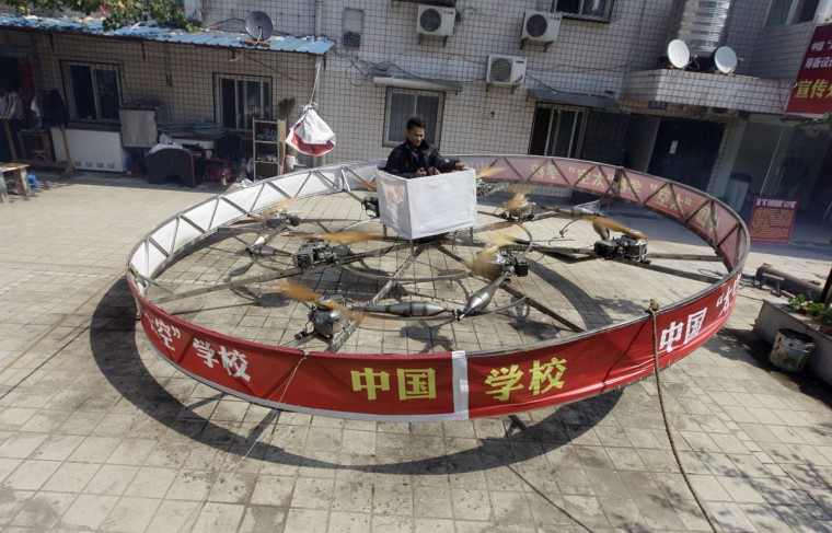 Local farmer Shu Mansheng hovers above the ground in his self-designed and homemade flying device during a test flight in front of his house in Dashu village on the outskirts of Wuhan, Hubei province on Sept. 21, 2011. The round steel flying device, which cost more than 20,000 yuan ($3,135), is the fifth model made by Shu, a junior middle school graduate. It measures around 5.5 meters (18 feet) in diameter, and is powered by eight motorcycle engines. Shu managed to hover for 10 seconds at about 1 meter (3.3 feet) above ground during a recent test flight. (Reuters photo)