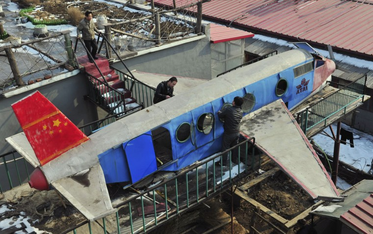 Li Jingchun (top), a 58-year-old farmer, looks on as his family members work on his home-made aircraft on top of his house in Xiahe village located in Shenyang, Liaoning province on Feb. 28, 2012. The 5m long, 1.5m wide plane, mostly made of recycled iron plates, cost the aircraft enthusiast and his family two years and more than 40,000 yuan ($6,349), according to local media. (REUTERS/Sheng Li)