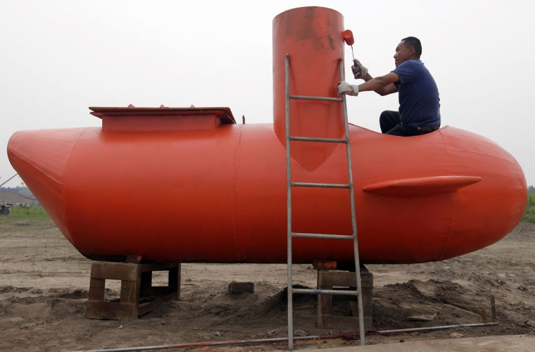 A worker paints a single-seater submarine designed by Zhang Wuyi and his fellow engineers at a shipyard in Wuhan, Hubei province on May 7, 2012. Zhang, a 37-year-old local farmer, who is interested in scientific inventions, has made six miniature submarines with several fellow engineers, one of which was sold to a businessman in Dalian at a price of 100,000 yuan ($15,855) last October. The submarines, mainly designed for harvesting aquatic products, such as sea cucumber, have a diving depth of 20-30 metres, and can travel for 10 hours, local media reported. (Reuters photo)