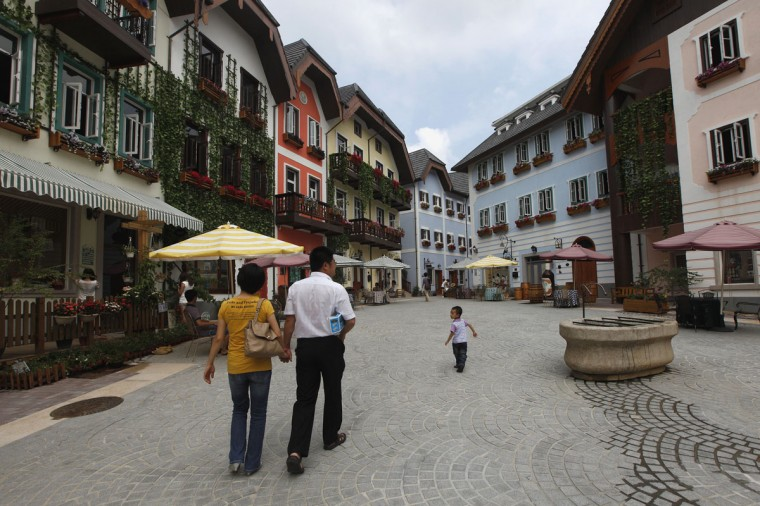 A family walks in the Chinese replica of Austria's UNESCO heritage site, Hallstatt village, in China's southern city of Huizhou in Guangdong province on June 1, 2012. (REUTERS/Tyrone Siu)