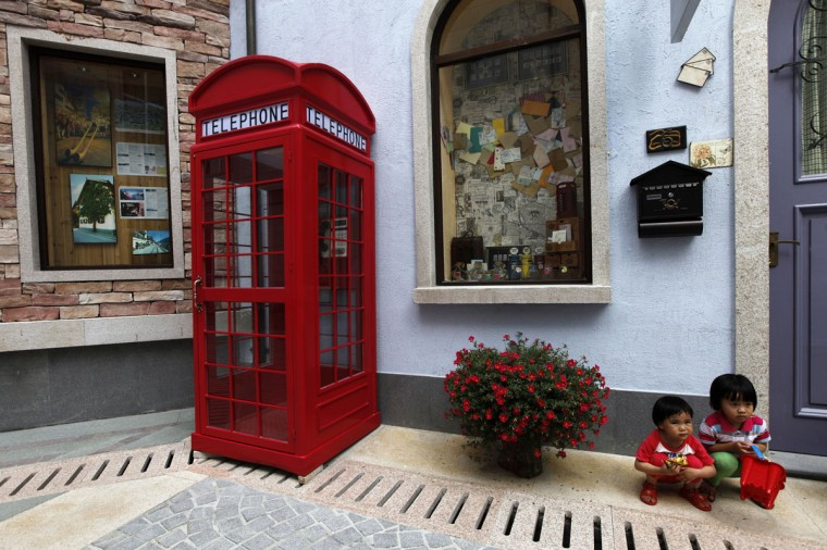 Children pose for pictures at the replica of Austria's UNESCO heritage site, Hallstatt village, in China's southern city of Huizhou in Guangdong province on June 1, 2012. Metals and mining company China Minmetals Corporation spent $940 million to build this controversial site and hopes to attract both tourists and property investors alike, according to local newspaper reports. (REUTERS/Tyrone Siu)