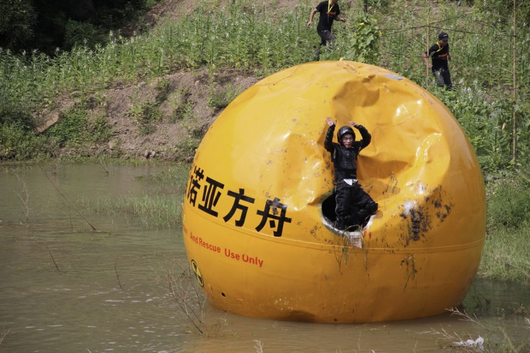 A Chinese inventor, Yang Zongfu, celebrates on his six-ton (5,443 kg) ball container named Noah's Ark of China after he succeeds in a series of tests of the vessel in Yiwu, Zhejiang province on August 6, 2012. According to local media, Yang spent two years and 1.5 million RMB (235,585 USD) to build this four-meter diameter vessel, which has been tested capable of housing a three-person family and sufficient food for them to live in 10 months. The vessel was designed to protect people inside from external heat, water and external impact. (REUTERS/China Daily)