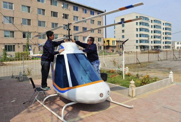 Tian Shengying (right), a 55-year-old blacksmith, adjusts the rotor of the helicopter, in Shenyang, Liaoning province on Sept. 21, 2012. Tian built the bottom, body, tail and rotor of the helicopter single-handedly without a detailed blueprint in just half a month after receiving a request by an unmanned aircraft research center. (REUTERS/Sheng Li)