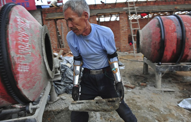 Sun Jifa moves a brick as he works to build his new house in Yong Ji county, Jilin province, on Sept. 25, 2012. Chinese farmer Sun, who lost his forearms in a dynamite fishing accident 32 years ago, could not afford to buy prosthesis. He spent two years guiding his two nephews to build him prosthesis from scrap metal, plastic and rubber. Over the years, Sun and his nephews have built about 300 prosthetic limbs for people in need, charging 3000 RMB ($476) each. (REUTERS/Sheng Li)