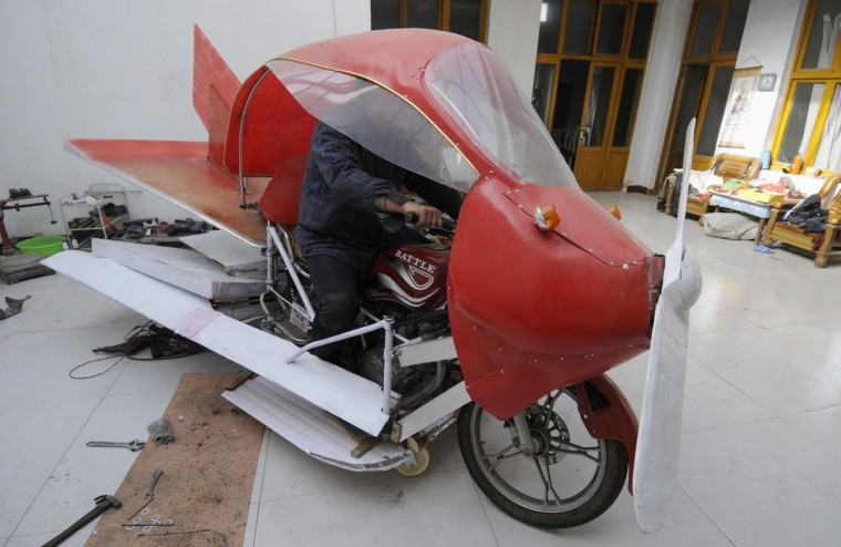Zhang Xuelin sits inside his home-made aircraft at his home before its test flight in Jinan, Shandong province, on Nov. 28, 2012. Zhang, a farmer who dropped out of primary school in his early years, spent around 2,000 yuan ($321) to build a plane around a motorcycle, using wood and plastic boards. The plane, which took 11 months to build, failed in its test flight. (REUTERS/China Daily)