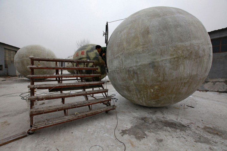 """Chinese inventor Liu Qiyuan speaks on his mobile phone as he sits in his spherical pod named """"Noah's Ark"""" in Xianghe, Hebei province on Dec. 12, 2012. Liu, who has spent 1.8 million yuan ($288,000) on building six """"Noah's Ark""""s in 8 months with the help of his former furniture factory's workers, is working on his seventh pod. The 17 cubic-meter volume vessels were built to serve as lifeboats in the event of earthquakes, tsunamis and floods. (REUTERS/Petar Kujundzic)"""
