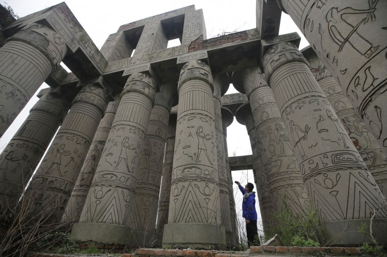 A visitor takes a photograph of a carved structure, which is a replica of the Karnak Temple in Egypt, at the abandoned Wanguo park in Wuhan, Hubei province on March 12, 2013. (REUTERS/Stringer)