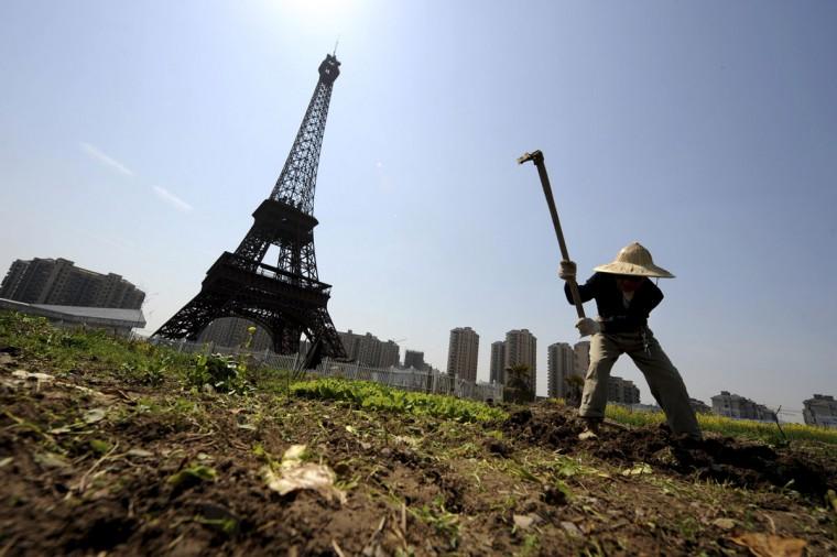 A farmer tills the field near the replica of the Eiffel Tower at the Tianducheng development in Hangzhou, Zhejiang province, March 21, 2014. (REUTERS/Lang Lang)