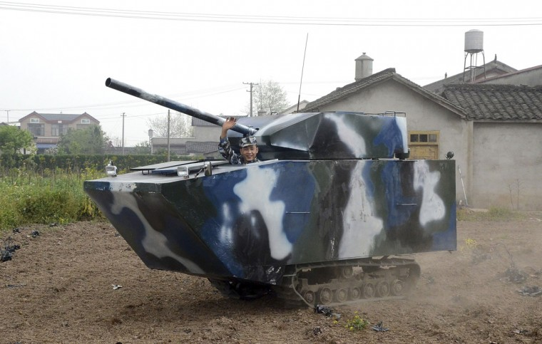"""Jian Lin, a 31-year-old farmer who used to serve in the Chinese navy, waves in his home-made replica of a tank during a trial run, at a village in Mianzhu, Sichuan province on April 9, 2014. The """"tank"""", which measures 4.5m long (15 feet), 1.6m wide (5 feet) and 2.1m high (7 feet), weighs nearly 3 tons and cost Jian about 40,000 yuan ($6,450) to make, local media reported. (Reuters photo)"""