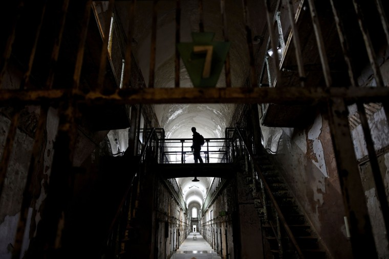 "A visitor wanders through block 7 of Eastern State Penitentiary in Philadelphia. Opened in 1829, with the original corrective system of ""confinement in solitude with labor,"" the penitentiary housed about 75,000 inmates in its 142 years of operation. At Eastern State reunions, former inmates, staff and guard gather to share memories and trade stories and get a chance to describe their experiences in question-and-answer sessions with the public. (REUTERS/Mark Makela)"
