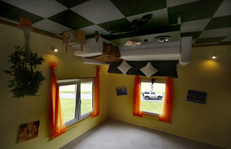 A car is seen through the living room window of the 'Crazy House', which is completely built upside-down, in the village of Affoldern. (REUTERS/Kai Pfaffenbach)