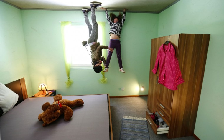 Dutch tourists Rosanna, left, and Nova pose for a photograph inside the bedroom of the 'Crazy House', which is completely built upside-down, in the village of Affoldern in Germany. (REUTERS/Kai Pfaffenbach)