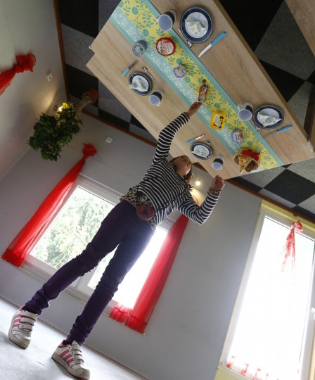 Dutch tourist Nova inspects the dining table inside the 'Crazy House', which is completely built upside-down, in the village of Affoldern. (REUTERS/Kai Pfaffenbach)