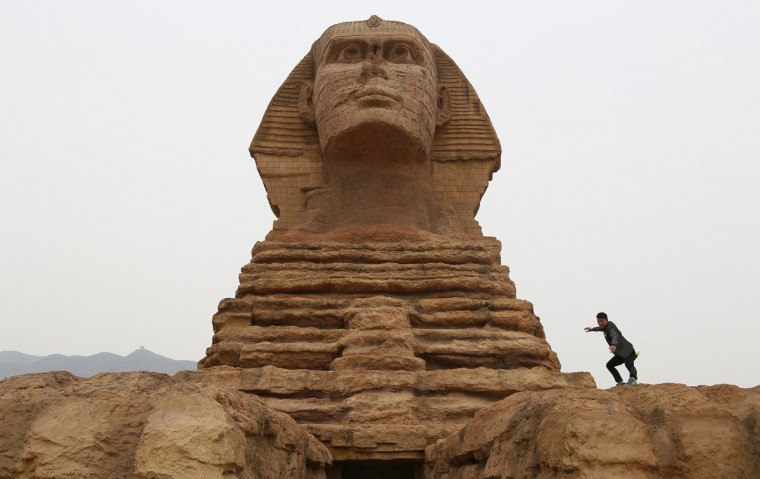 A man poses for photographs on a full-scale replica of the Sphinx, that is part of an unfinished theme park that will also accommodate the production of movies, television shows and animation, on the outskirts of Shijiazhuang, Hebei province on May 10, 2014. (REUTERS/Stringer)