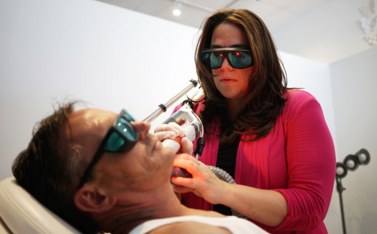 "James Ward has a tribal tattoo removed from his face with a laser by Jill France at her ""What Were You Inking"" clinic in downtown Denver. (REUTERS/Rick Wilking)"