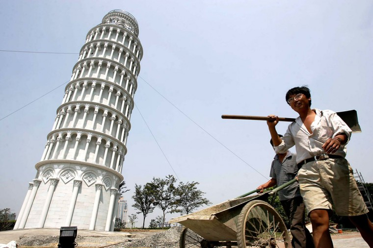"""Chinese workers walk past a 1:4 scale mini leaning tower of Pisa in Shanghai, September 7, 2004. The financial hub of Shanghai in eastern China holds a carnival called """"Roman Holiday"""" featuring Italian cluture, architectures, fashion and food from September 10 to October 24. (REUTERS/China Photos)"""
