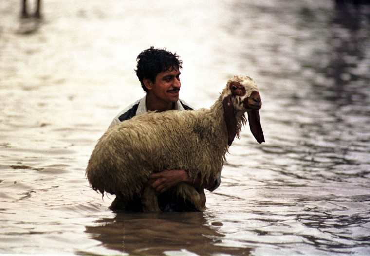 A Pakistani man carries his sheep down a flooded road after a heavy downpour in the provincial capital of the Punjab, Lahore, on July 24, 2001. (REUTERS/Mohsin Raza)