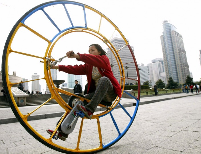"""A woman rides an unicycle at a park in Shanghai on Feb. 28, 2004. The unicycle was designed several years ago by Chinese inventor Li Yongli, who called it """"the number one vehicle in the world."""" (Reuters photo)"""