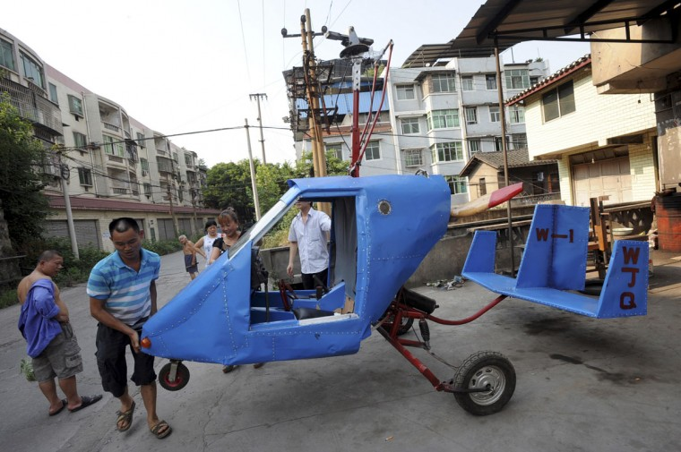 Wen Jiaquan (second from left), 54-year-old motorcycle mechanic, moves his home-made helicopter in Qingping township of Chongqing municipality, on July 28, 2013. Wen and his family spent over 10,000 yuan (1,630 USD) and more than three months to build this 4.2-meter-long, 2.8-meter-high helicopter using mostly motorcycle components and a used car engine, local media reported. (Reuters photo)