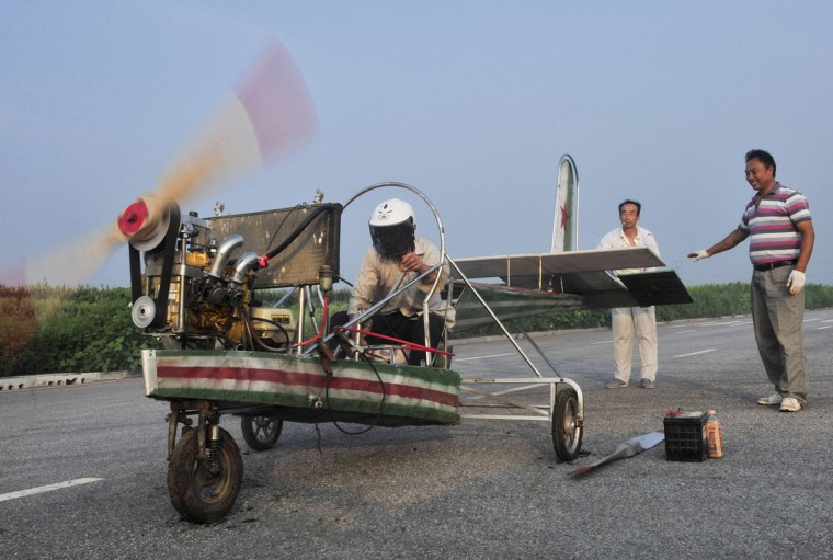 Ding Shilu tests the engine of his home-made aircraft before conducting a test flight on the outskirts of Shenyang, Liaoning province, on Aug. 6. 2013. Ding, a 65-year-old migrant worker, spent around 2,000 yuan ($327) to build this 5-meter-long, 4.5-meter-high plane using components from motorcycles and electric bicycles. Ding failed his fourth test flight on Tuesday since he started his project four years ago, local media reported. (REUTERS/Sheng Li)